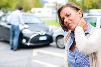 Woman grasping her neck after an accident