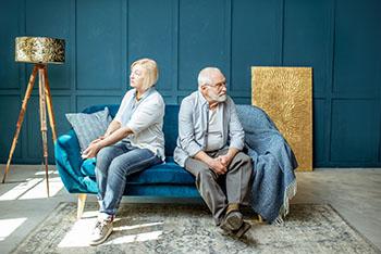 Older couple sitting apart looking sad