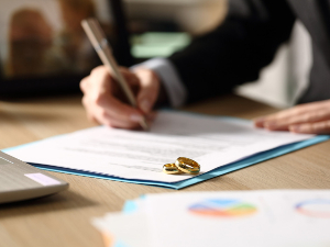 Attorney signing documents with wedding rings on top of the document