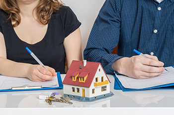 Man and woman filling out divorce paperwork with a house and keys in front of them