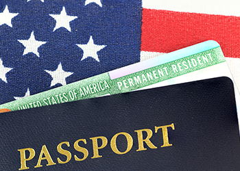 Permanent resident card and passport lay on top of American flag