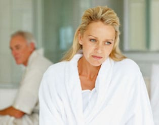 Sad woman with husband in the background