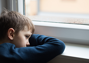A boy rests his head on a window sill