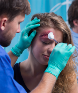 Nurse tending to wound above a woman's eye