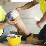Worker tending to co-worker with knee injury