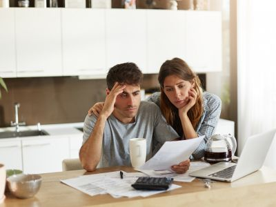 Unhappy Couple Looking Through Bills