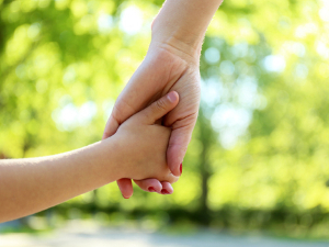 Parent's hand holding the hand of a child