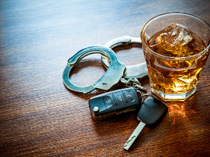 Whiskey glass on table next to car keys