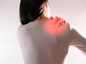 Woman reaching for her right shoulder in pain