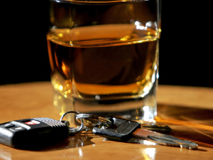 Whiskey glass on table with car keys