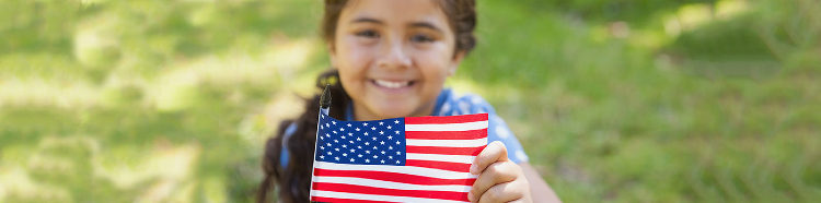 Girl smiling and holding a little American flag