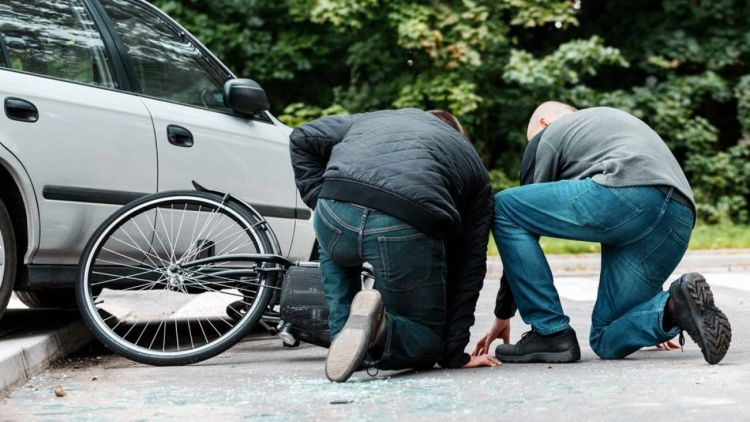 Two people bent over near a bike and car collision