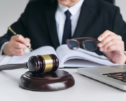 Attorney writing on document with a gavel and laptop nearby