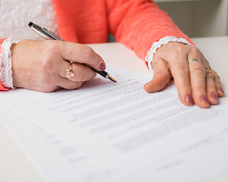Elderly woman signing a document