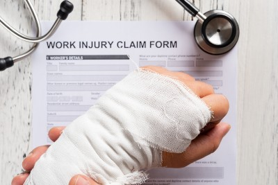 Bandage-wrapped Wrist Over a Work Injury Claim Form