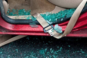 Floorboard of a vehicle covered in shattered glass