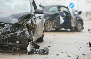 Two cars that look pretty damaged after crashing into each other