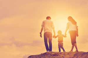Family walking while holding hands with the sun in the background