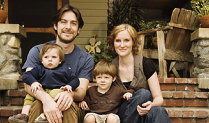 Photo of a family smiling while sitting on porch steps