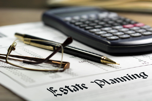 Estate planning document with a calculator, pen, and pair of glasses
