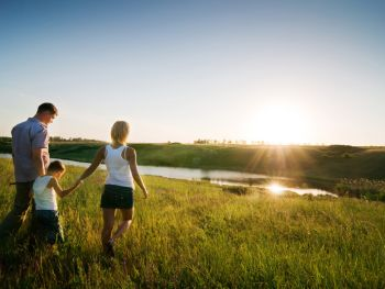 Two parents holding their child's hand in a field at sunset