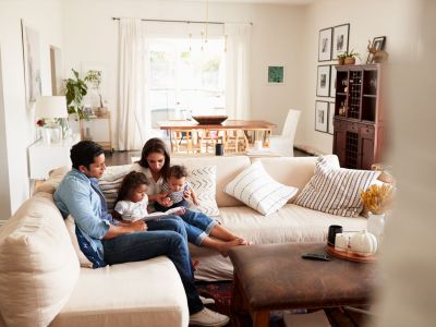 Family of four sitting in their living room reading together