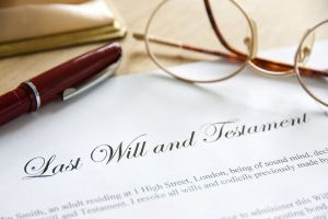 Last Will and Testament with a pen and glasses sitting on top