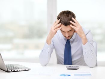 Stressed out man holding head in front of calculator and laptop