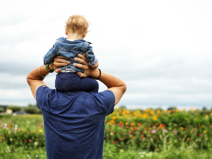 Father holding son on his shoulders in a field