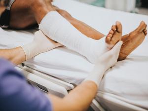 Nurse tending to a patient's leg in a cast
