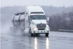 Semi-truck driving down the highway on a cold and rainy day