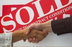 Handshake in front of sold signs