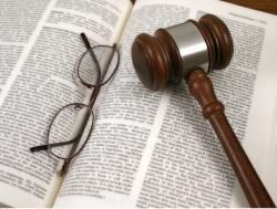 Law book with gavel and glasses