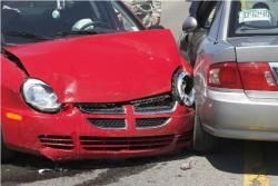 Car with a smashed front-end up against another damaged car