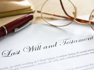 Last Will and Testament typed in cursive on a page with glasses and pen laid on top