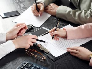 Three people's hands with pens pointing to clipboard