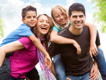 Happy family of four with one child piggy-backing on each parent's back