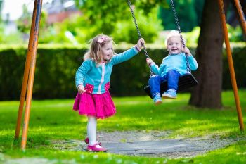 Two Young Children Swinging on a Swing
