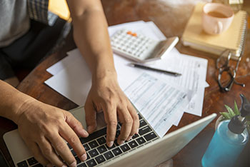Man working on computer with tax documents next to him