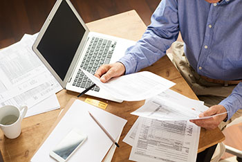 Man working on tax documents with his computer and documents on a desk