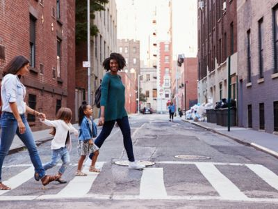 Two moms with two young girls holding hands crossing the street