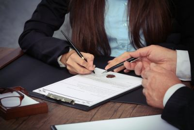 Woman in suit and man in suit pointing pens at a papers on a clipboard