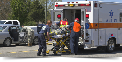 EMT's putting man on a stretcher into an ambulance