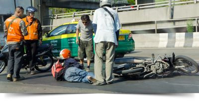 Man laying on ground in the street next to a motorcycle with people coming to help