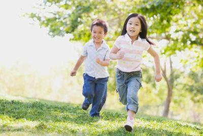 Two Happy children running through a field