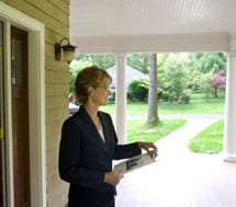 Woman holding clipboard on the porch of a house