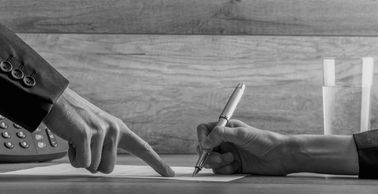 hand pointing where to write and hand with pen writing; in black and white