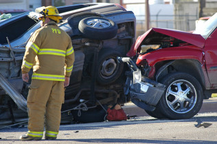 Firefighter standing at the scene of a car accident