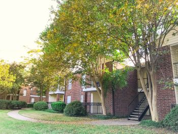 Two story apartment complex with autumn colored trees outside