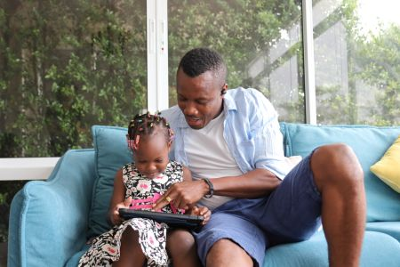 Father spending time with his daughter on a tablet